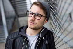Modern young man listening to music with earphones in the street Royalty Free Stock Image