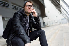 Modern young man listening to music with earphones in the street Stock Photos