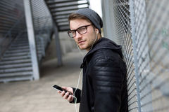Modern young man listening to music with mobile phone in the street. Stock Photography
