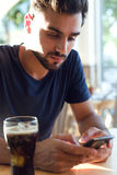 Modern young man with mobile phone in cafe. Royalty Free Stock Photo