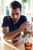 Modern young man with mobile phone in cafe. Royalty Free Stock Images