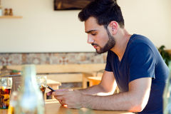 Modern young man with mobile phone in cafe. Stock Photography