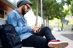 Modern young man with mobile phone in the street. Royalty Free Stock Images