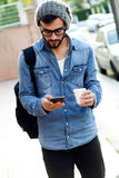 Modern young man with mobile phone in the street. Stock Images