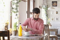 Modern young man sitting at coffee shop Stock Photo