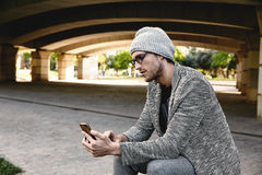 Modern young man with smartphone under bridge Stock Image