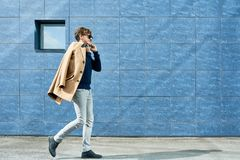 Modern young Man Speaking by Phone in City. Full length portrait of handsome young man wearing sunglasses speaking by phone and smiling happily while walking in Royalty Free Stock Image