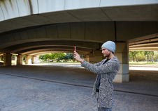 Modern young man with tablet pc under a bridge Royalty Free Stock Image