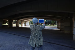 Modern young man with tablet pc under a bridge Stock Photography