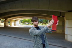 Modern young man with tablet under a bridge Stock Photo