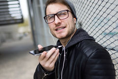 Modern young man talking on the phone with hands free in the street. Stock Image