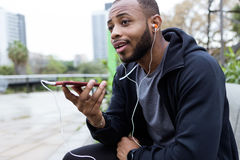 Modern young man talking on the phone with hands free in the street. Stock Photography