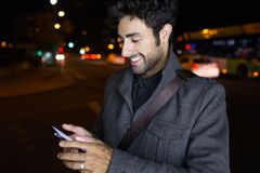 Modern young man using his mobile phone in the street at night. Stock Images