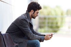 Modern young man using his mobile phone in the street. Stock Photography