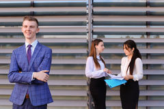 Modern young masculine guy businessman, student in foreground in. Handsome confident young male guy businessman, office worker, student posing and smiling in Royalty Free Stock Photography