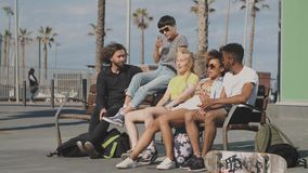 Trendy young friends on bench on street stock video footage