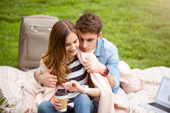 Modern young people in a park. Being close. Delighted and sweat young lovely couple sitting on the grass in the park, arming each other and drinking coffee while Royalty Free Stock Photos