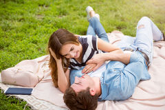 Modern young people in a park. Love you thousand times. Happy and merry young lovely couple laying on the grass in the park and arming each other Royalty Free Stock Images