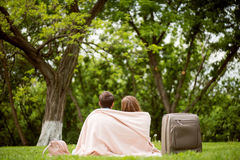 Modern young people in a park. Only together. Sweat young lovely couple sitting on the grass in the park with a blanket while arming each other Royalty Free Stock Photography