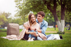 Modern young people in a park. Warm atmosphere. Smiling and cheerful young lovely couple sitting on the grass in the park, arming each other and drinking coffee Royalty Free Stock Image