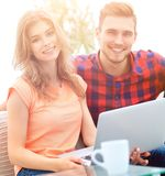 Modern young people using laptop at home. Smiling modern young people using laptop at home Royalty Free Stock Photography