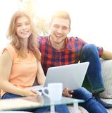 Modern young people using laptop at home. Smiling modern young people using laptop at home Stock Photo