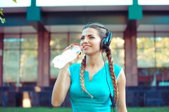 Sportive woman in headphones drinking water royalty free stock photo
