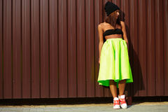 Modern young stylish woman in bright modern cloth. Modern young stylish woman girl  model in bright modern cloth in green colotful skirt outdoors in the street Stock Photo