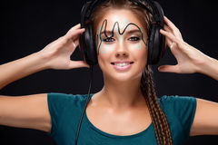 Modern young woman with art makeup enjoys listening to music in headphones. Positive emotions, leisure. Copy space. Stock Image