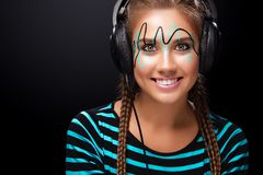 Modern young woman with art makeup enjoys listening to music in headphones. Positive emotions, leisure. Copy space. Stock Photography