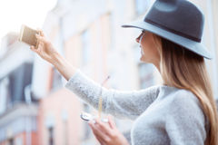 Modern young woman in a big city. Making selfie.  Smiling and merry modern young woman using a smartphone and making a selfie while being outside Royalty Free Stock Photos