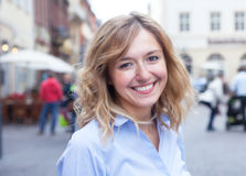 Modern young woman with curly blond hair in the city Royalty Free Stock Image