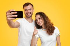 Content couple taking selfie on yellow background royalty free stock photos