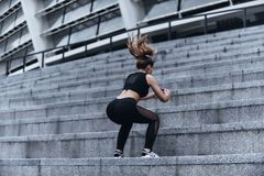 Full of energy. Modern young woman in sport clothing jumping while exercising on the stairs outdoors royalty free stock photo
