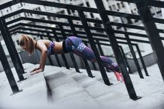Sport is the way of her life. Modern young woman in sport clothing keeping plank position while exercising on the steps outdoors stock images