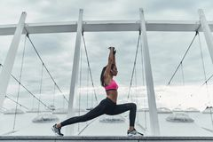Balancing her mind and body. Modern young woman in sports clothing stretching while warming up outdoors stock photos