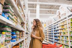 Modern young woman with a tablet selects baby food in supermarket.  Royalty Free Stock Photos