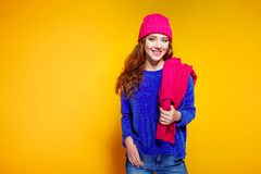 Modern young woman wearing blue sweater and pink hat, and scarf posing, making funny facial expression. stock photography