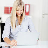 Modern young woman working on her laptop. Modern young woman sitting at a desk working on her laptop reading information on the screen with a smile Stock Photo