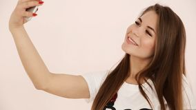 Modern youth. beautiful long-haired European-looking girl with brown hair does selfie on a smartphone near a white wall.  stock footage