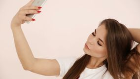 Modern youth. beautiful long-haired European-looking girl with brown hair does selfie on a smartphone near a white wall.  stock video footage