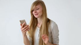 Modern youth. beautiful long-haired girl of European appearance with blond hair expressively talking on a video. Communication smartphone near the white wall stock footage