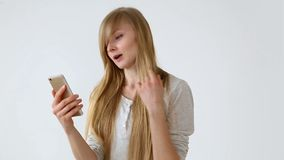 Modern youth. beautiful long-haired girl of European appearance with blond hair expressively talking on a video. Communication smartphone near the white wall stock video footage
