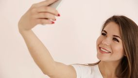 Modern youth. beautiful long-haired girl of European appearance with brown hair expressively talking on a video. Communication smartphone near the white wall stock footage