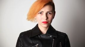 Modern youth. calm portrait of a serious woman of unusual appearance with red hair and creative hairstyle in a leather. Jacket stock video