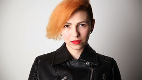 Modern youth. calm portrait of a serious woman of unusual appearance with red hair and creative hairstyle in a leather. Jacket stock video footage
