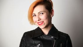 Modern youth. calm portrait of a smiling woman of unusual appearance with red hair and creative hairstyle in a leather. Jacket stock video footage