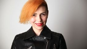 Modern youth. calm portrait of a smiling woman of unusual appearance with red hair and creative hairstyle in a leather. Jacket stock video