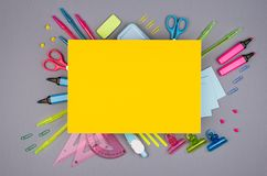 Modern youth office supply - neon blue, pink, yellow, green stationery and yellow paper with copy space on grey desk background. Royalty Free Stock Photography