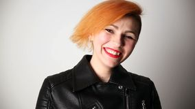 Modern youth. portrait of a laughing woman of unusual appearance with red hair and creative hairstyle in a leather. Jacket stock video footage